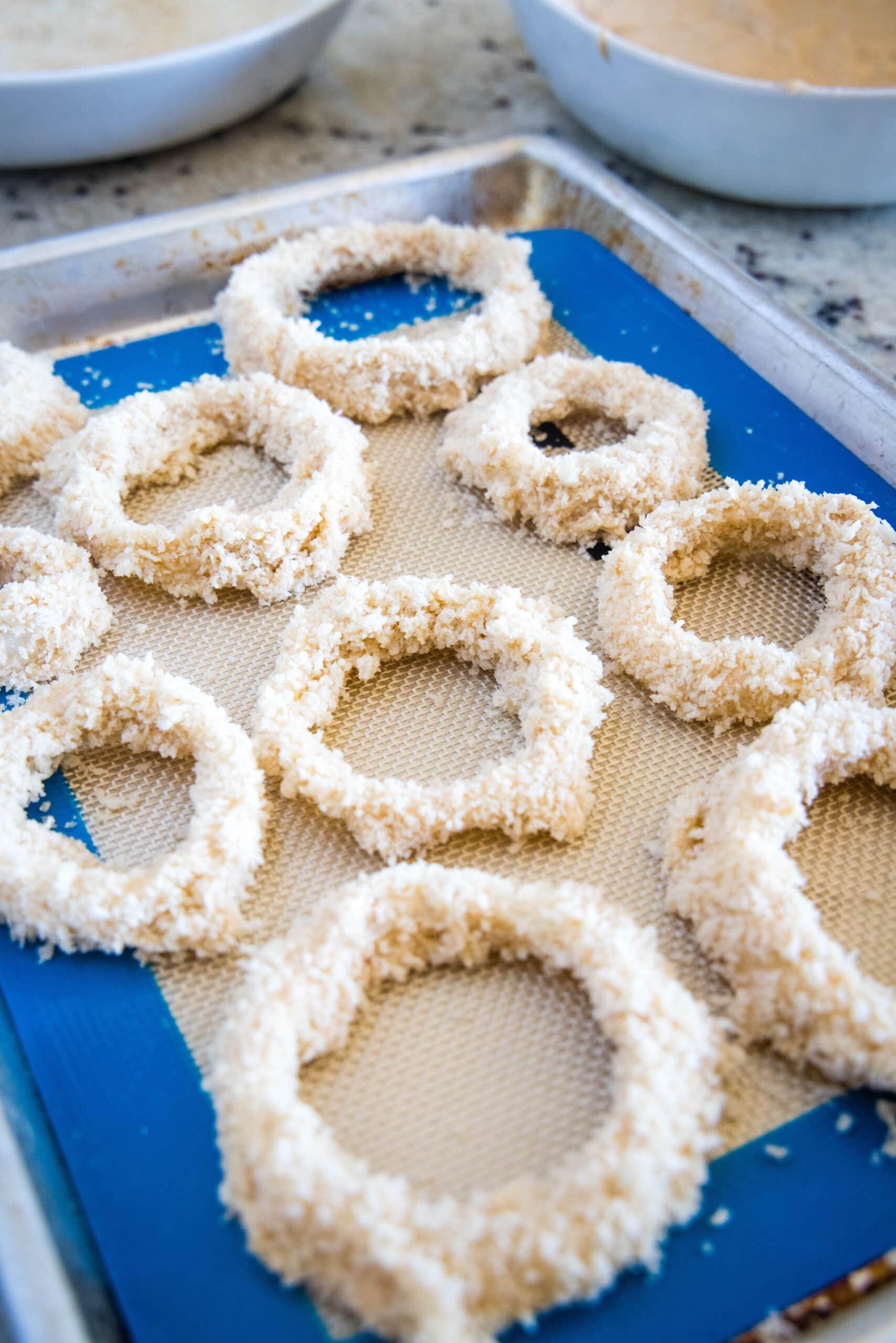 coated onion rings on baking sheet