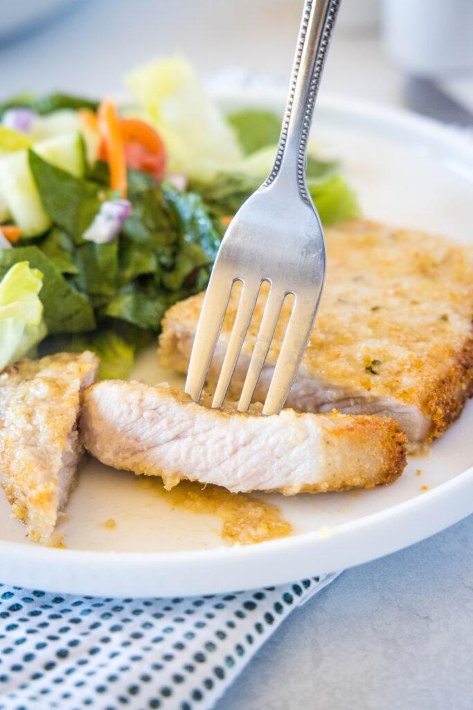 sliced pork chop on a plate with a fork