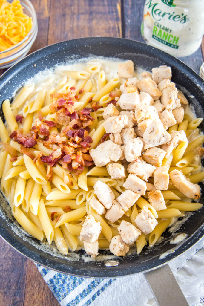 adding chicken, pasta, and bacon back to the ranch sauce in the pan