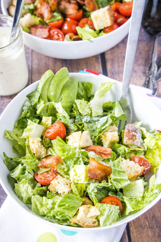 tossed blt salad in a bowl with fork