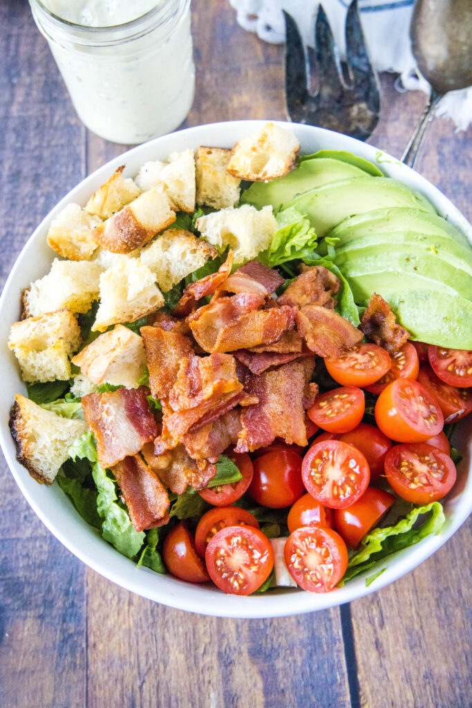 looking down on bowl with bacon, lettuce, tomato, croutons and avocado
