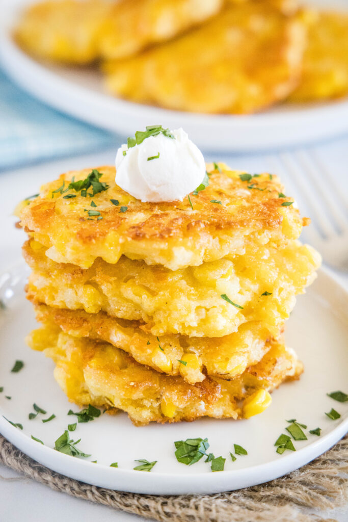 stack of corn fritters on a plate topped with sour cream