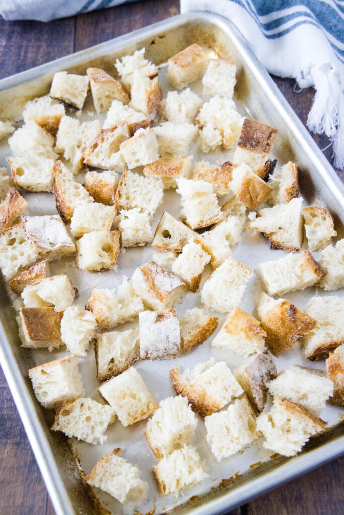 looking down at bread cubes on a baking tray