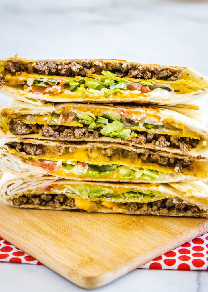 crunchwrap supreme copycat cut in half and stacked on cutting board