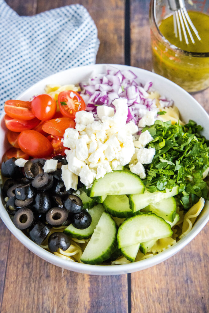 toppings for greek pasta salad arranged in a bowl