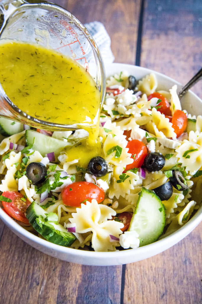 pouring greek dressing over a bowl of pasta salad