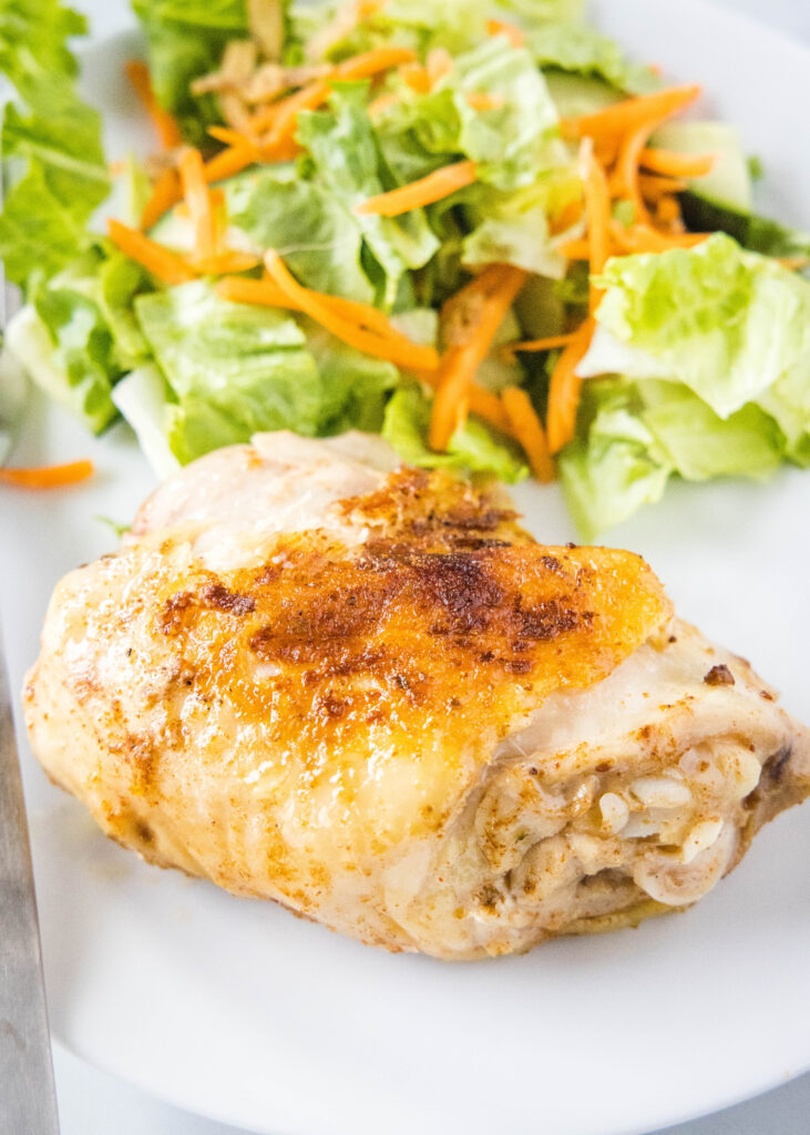 seared chicken thigh in a plate with salad