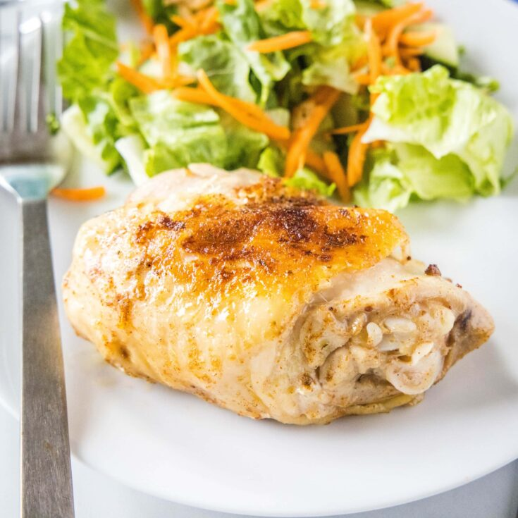 close up of cooked chicken thigh on a plate with salad