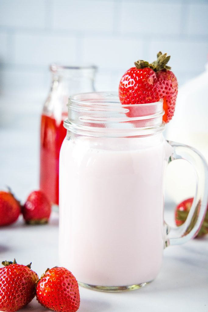 cup of strawberry milk with strawberry on rim of glass