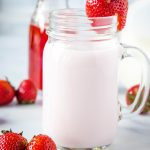 close up of strawberry milk with strawberry on rim of glass
