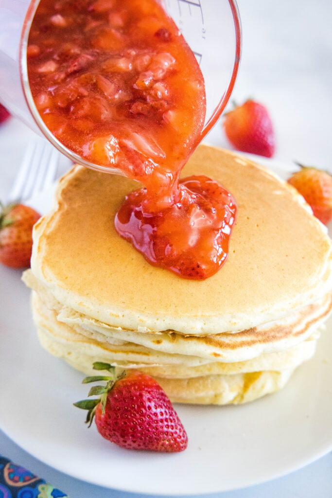 pouring strawberry sauce over pancakes