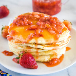 close up stack of pancakes with strawberry sauce