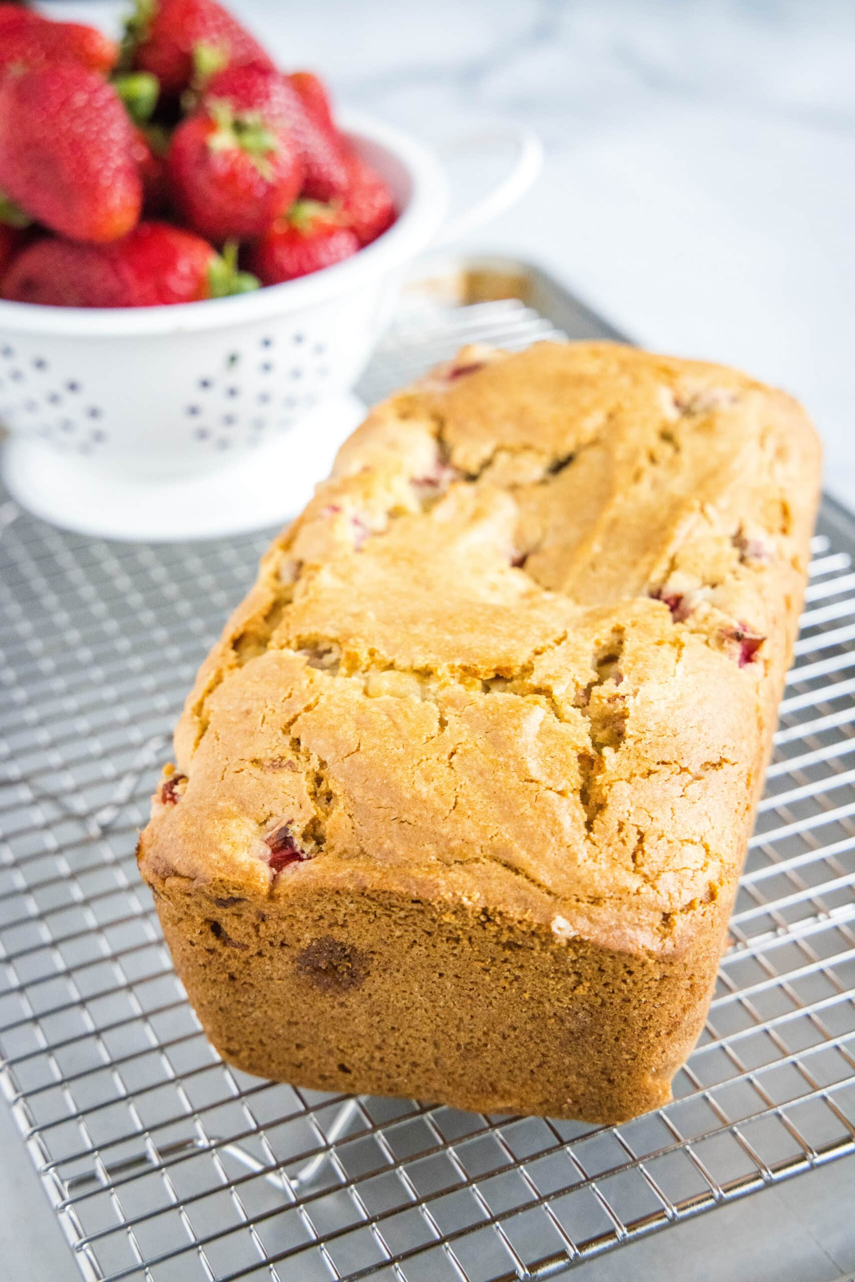 loaf of strawberry bread on cooling rack