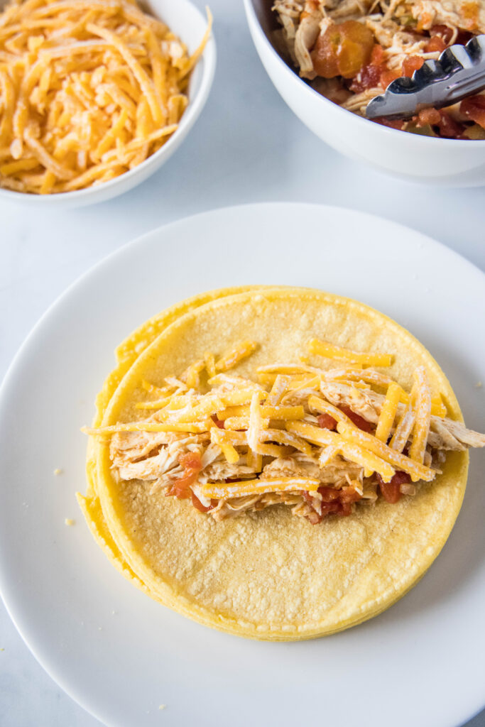 filling corn tortillas with chicken and cheese