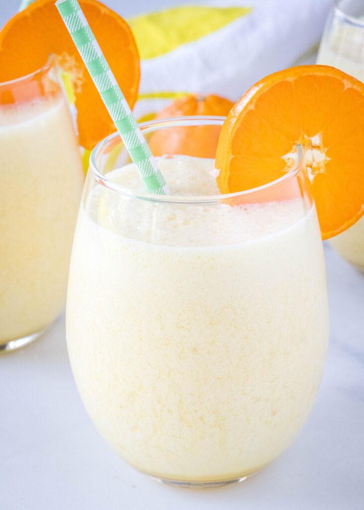 a glass of copycat orange julius with an orange slice