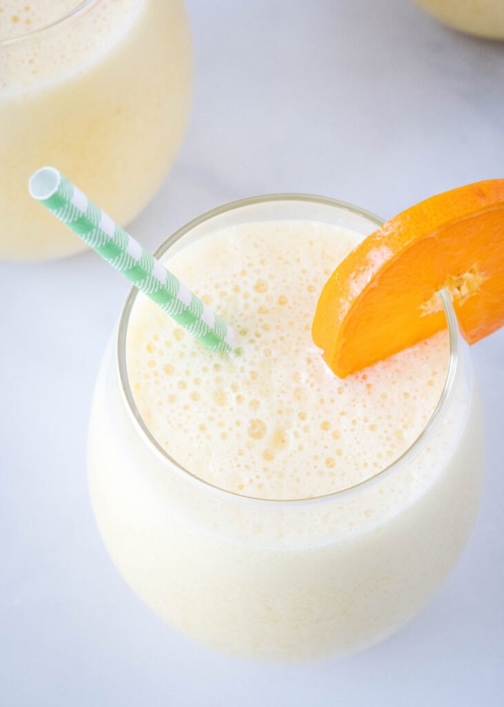 looking down on a frothy orange drink in a glass