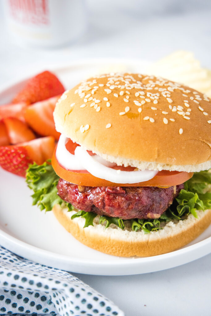 looking down on a plate with a smoked hamburger on a bun with a plate of strawberries