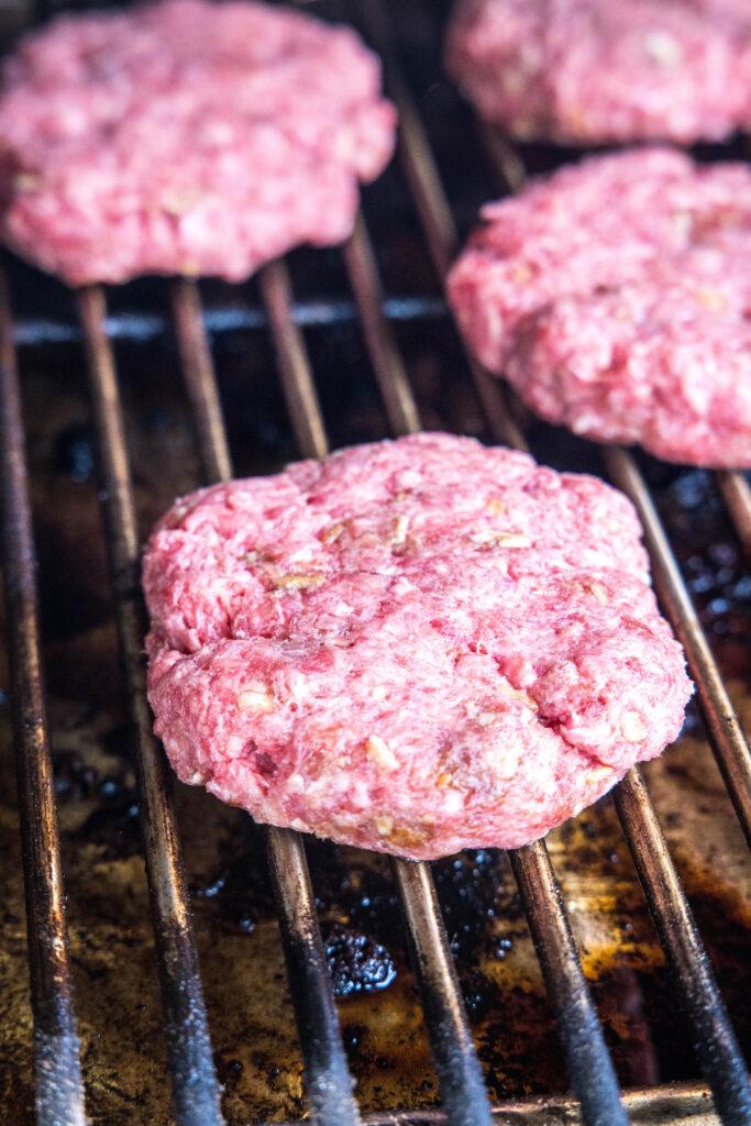 uncooked hamburgers on the smoker