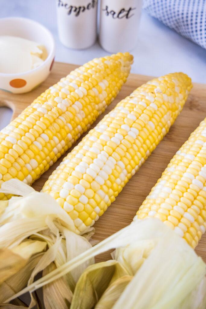 3 ears of corn on a cutting board