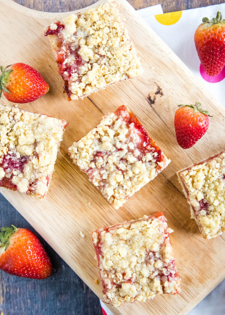 looking down on strawberry crumb bars on a cutting board
