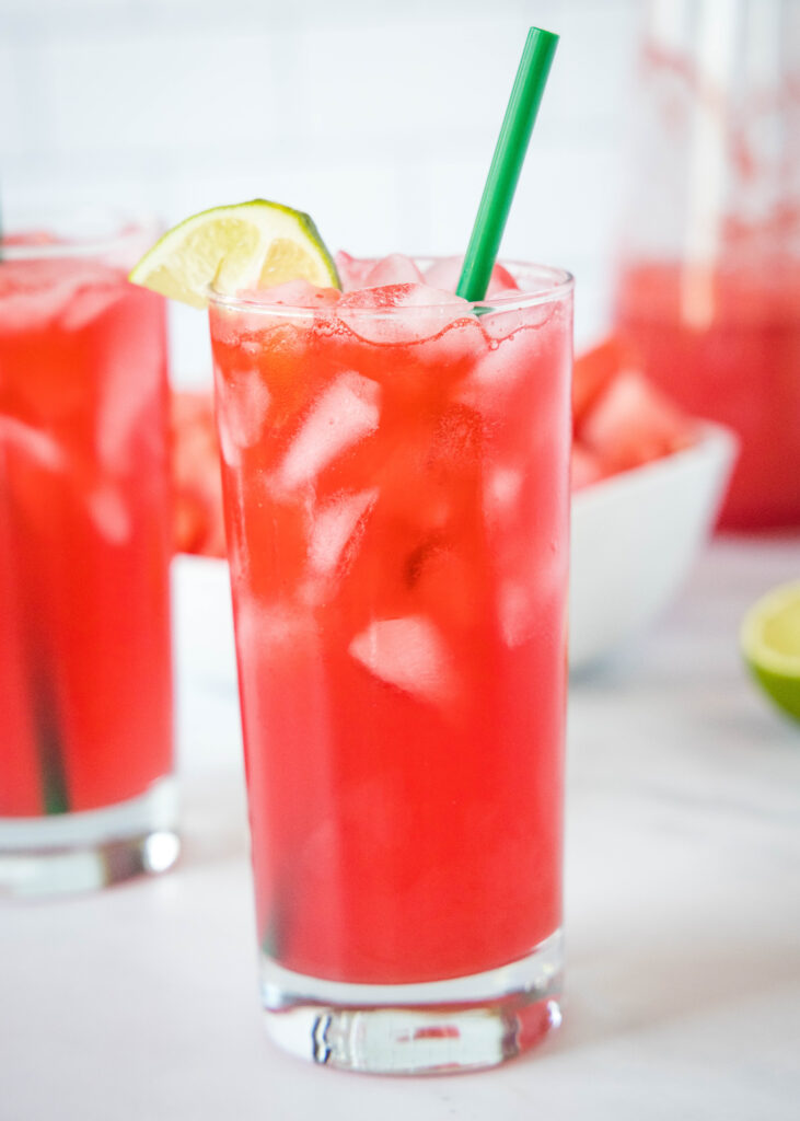 a glass filled with watermelon soda and a straw