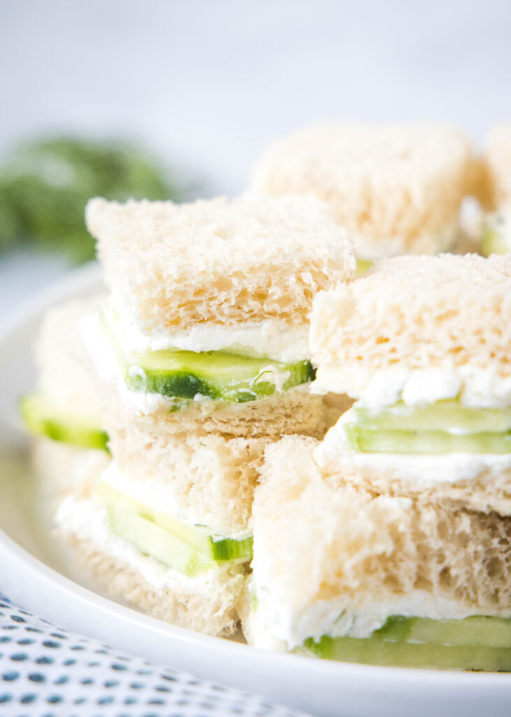 a stack of tea sandwiches on a white plate
