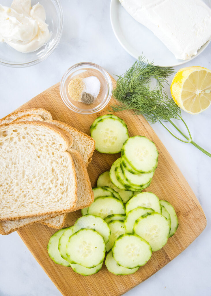 a cutting board with ingredients to make cucumber sandwiches