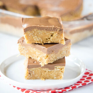 cropped in peanut butter oatmeal bars with chocolate frosting stacked on a plate