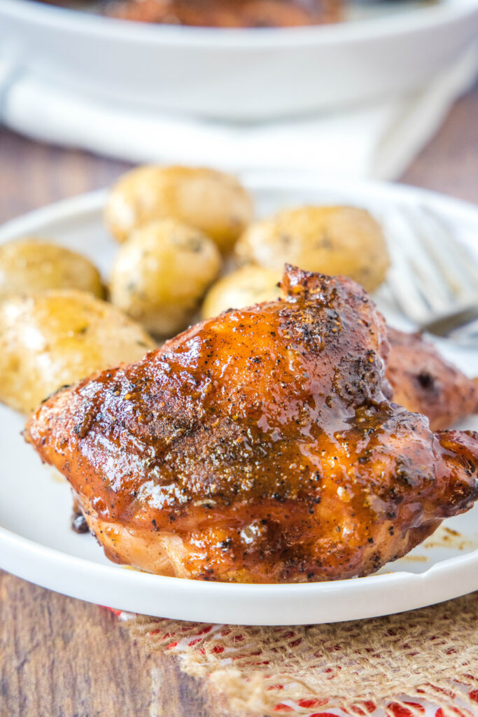 smoked chicken thigh on a plate with potatoes