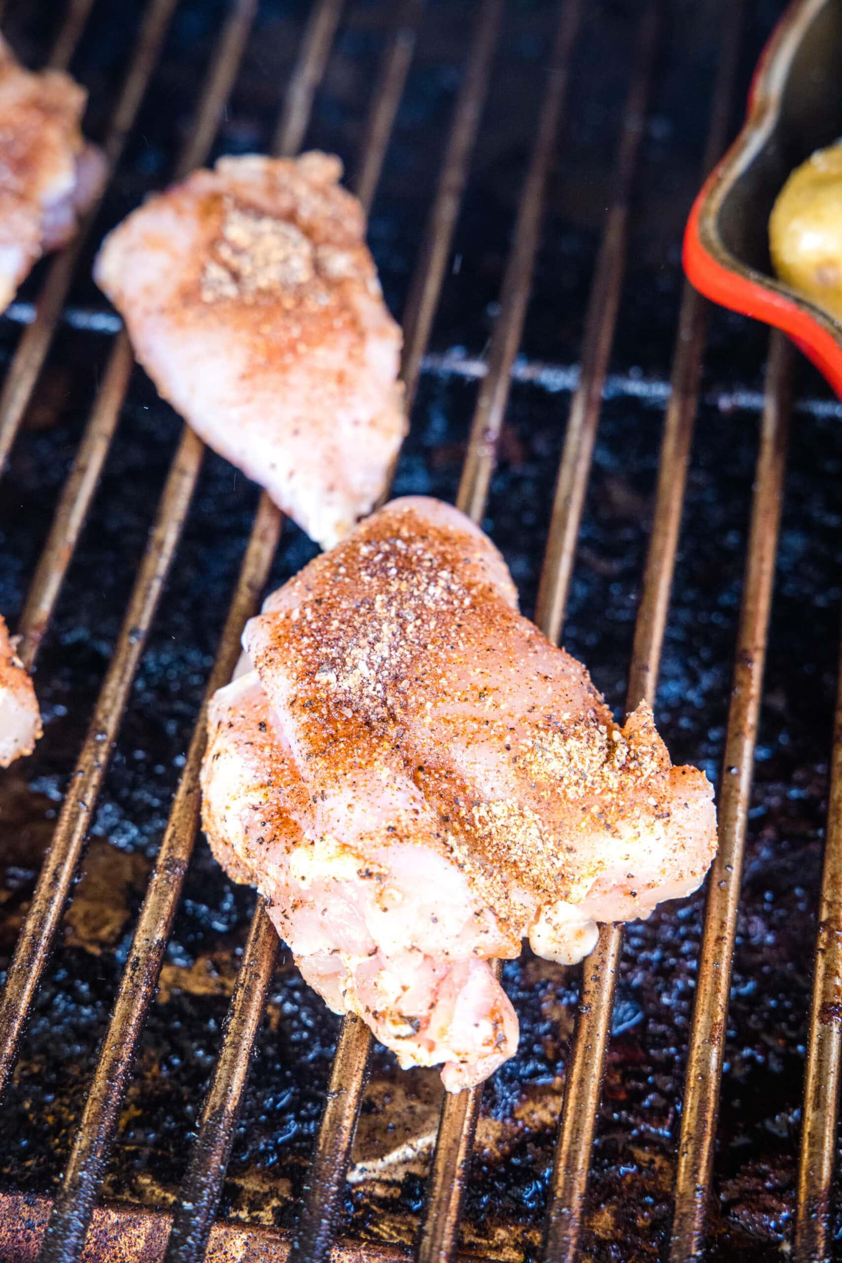 putting seasoned chicken thighs on the smoker