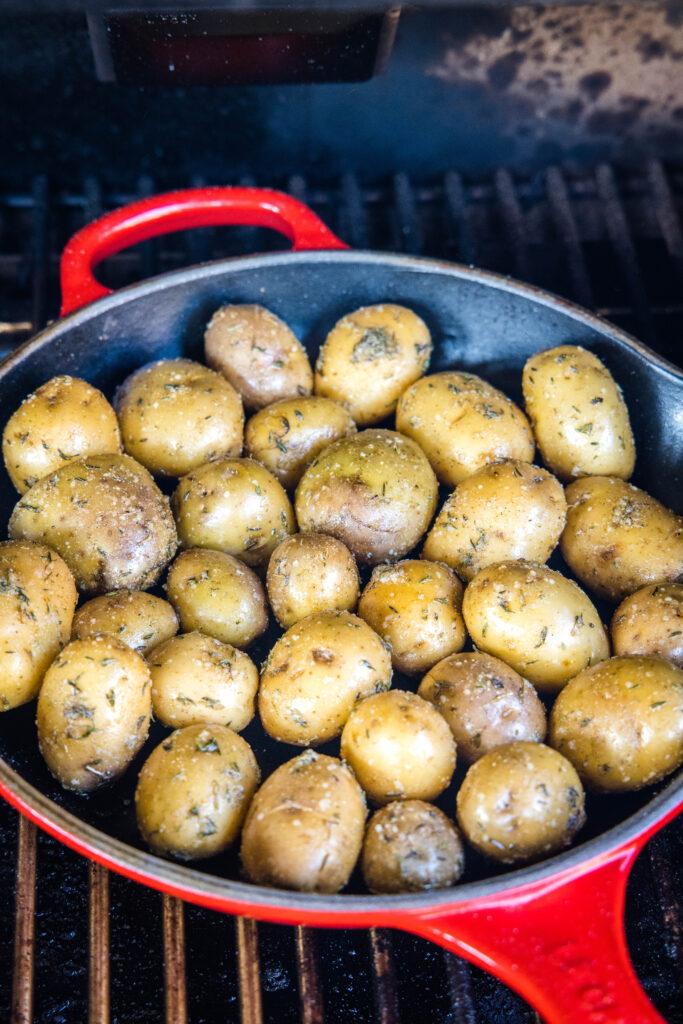 a pan of potatoes on the smoker