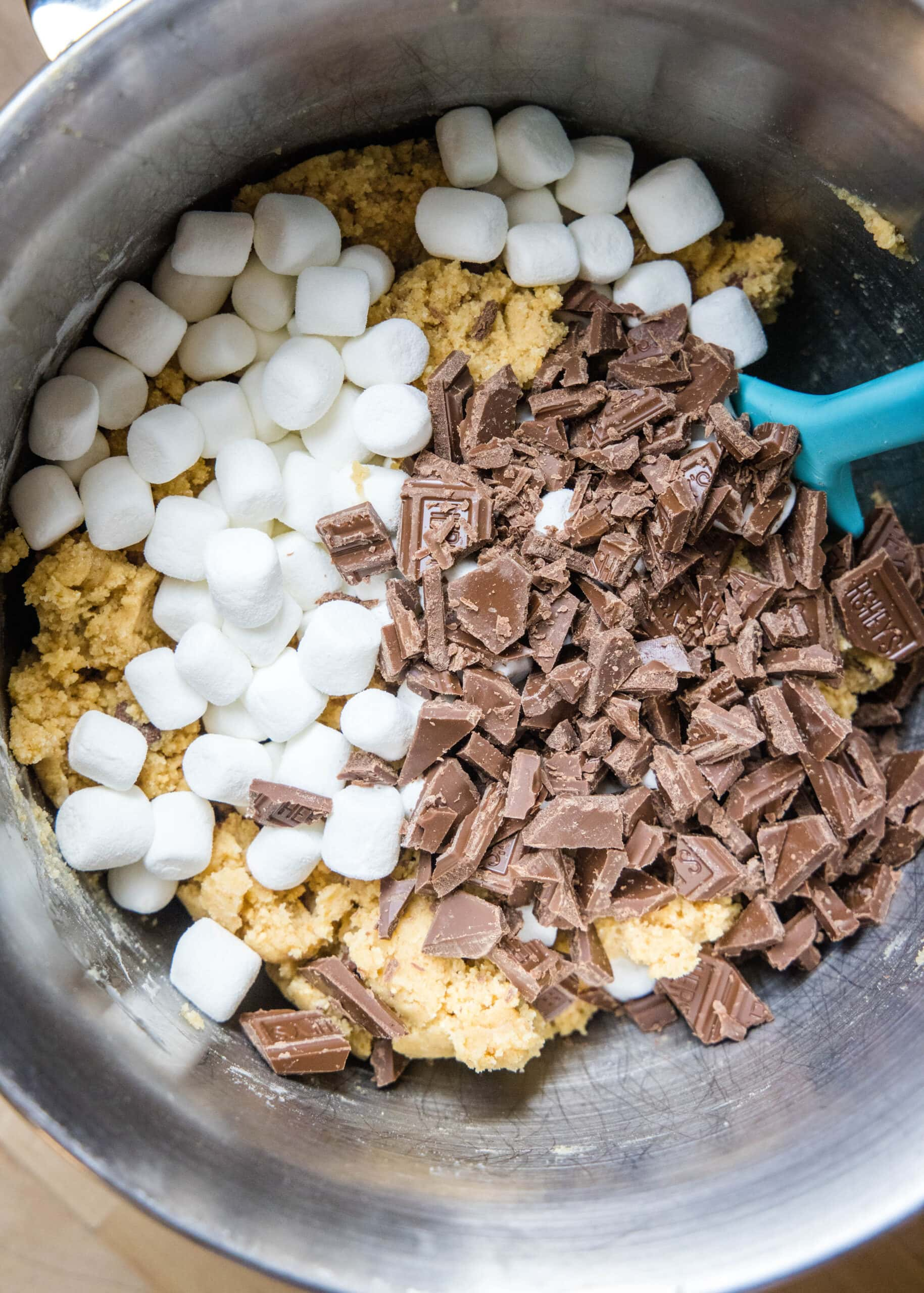 cookie dough in a mixing bowl with chocolate and marshmallows on top