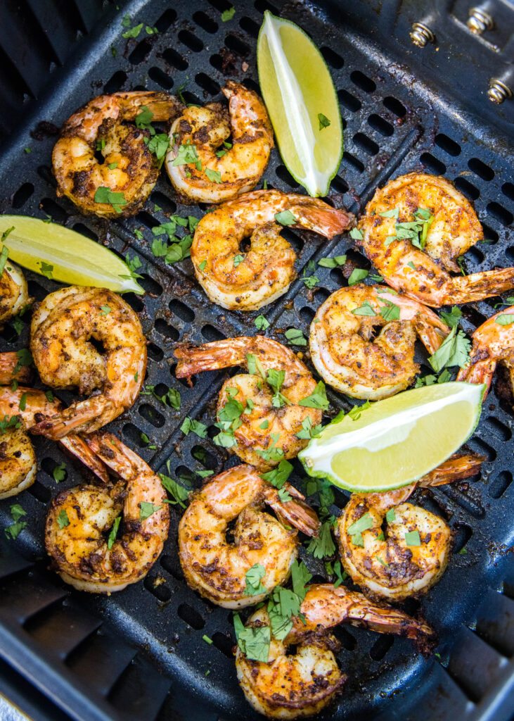 shrimp cooked in the air fryer sprinkled with cilantro and lime wedges