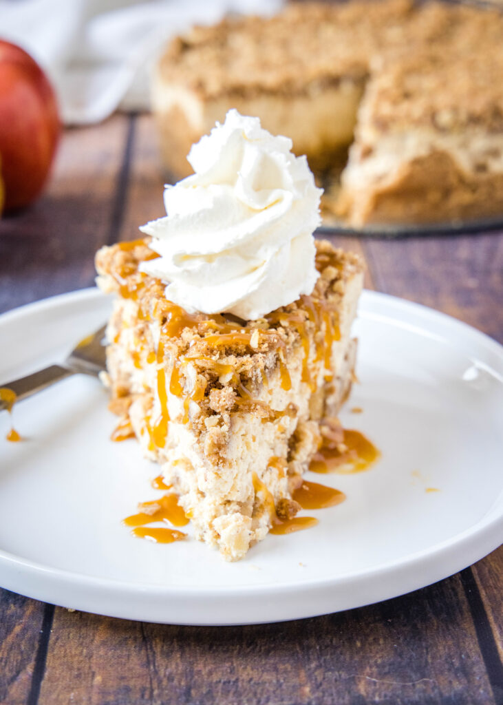 apple cheesecake on a plate with whipped cream