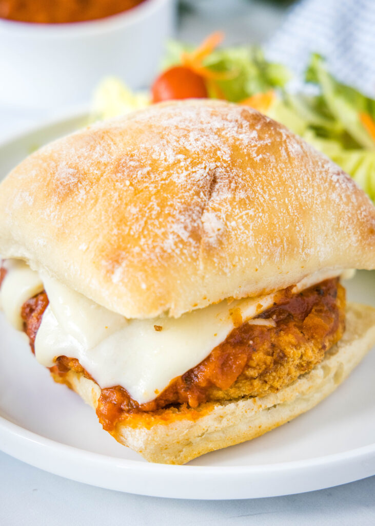 looking down on chicken parmesan sandwich on white plate