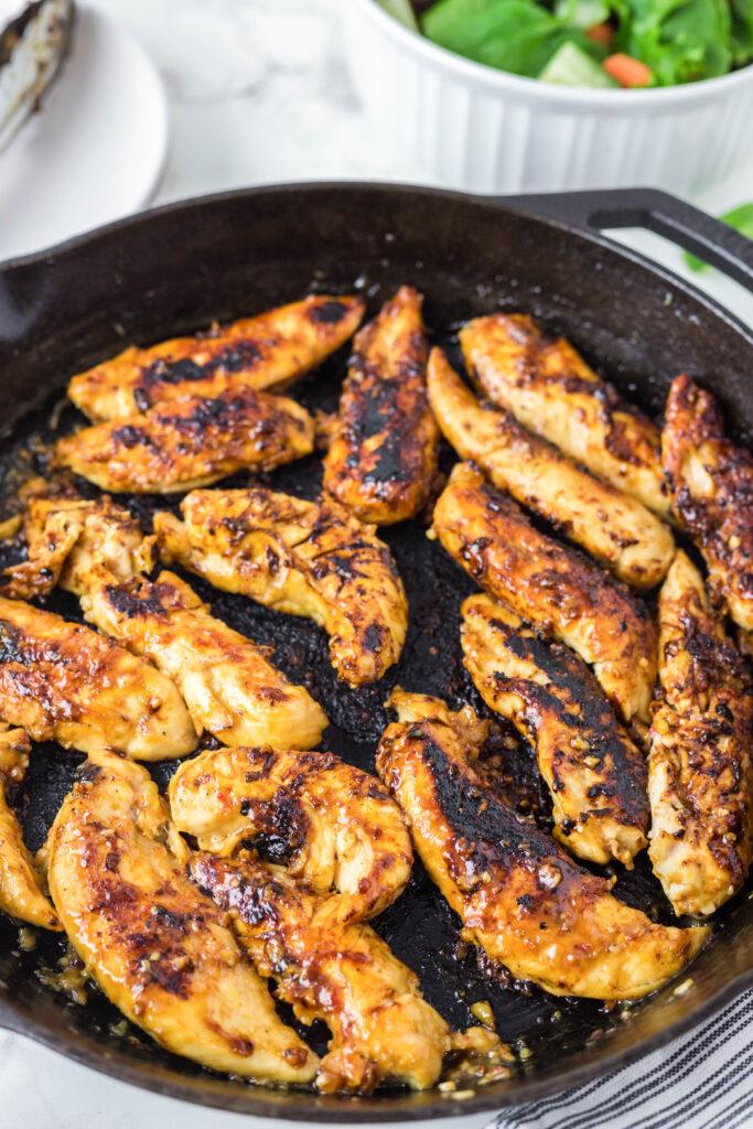 chicken tenders cooking in a skillet