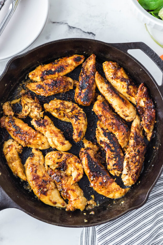 looking down on a cast iron skillet on with chicken tenders
