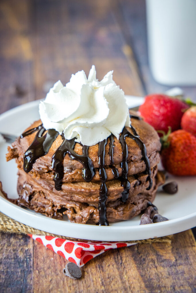 plate of chocolate pancakes with chocolate sauce and whipped cream
