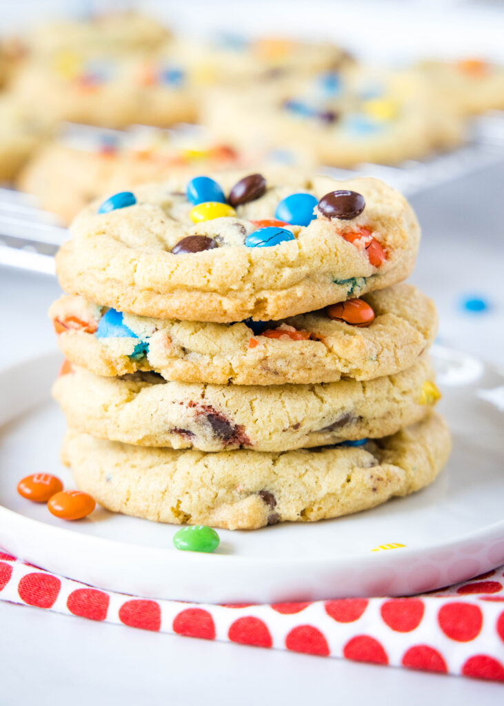 M&M cookies stacked on a white plate