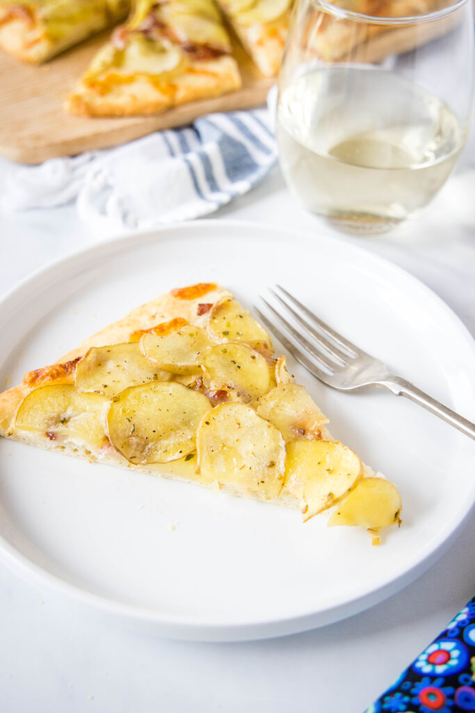 slice of potato pizza on a white plate with a fork