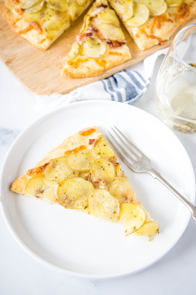 looking down on a slice of potato pizza with a fork on a white plate
